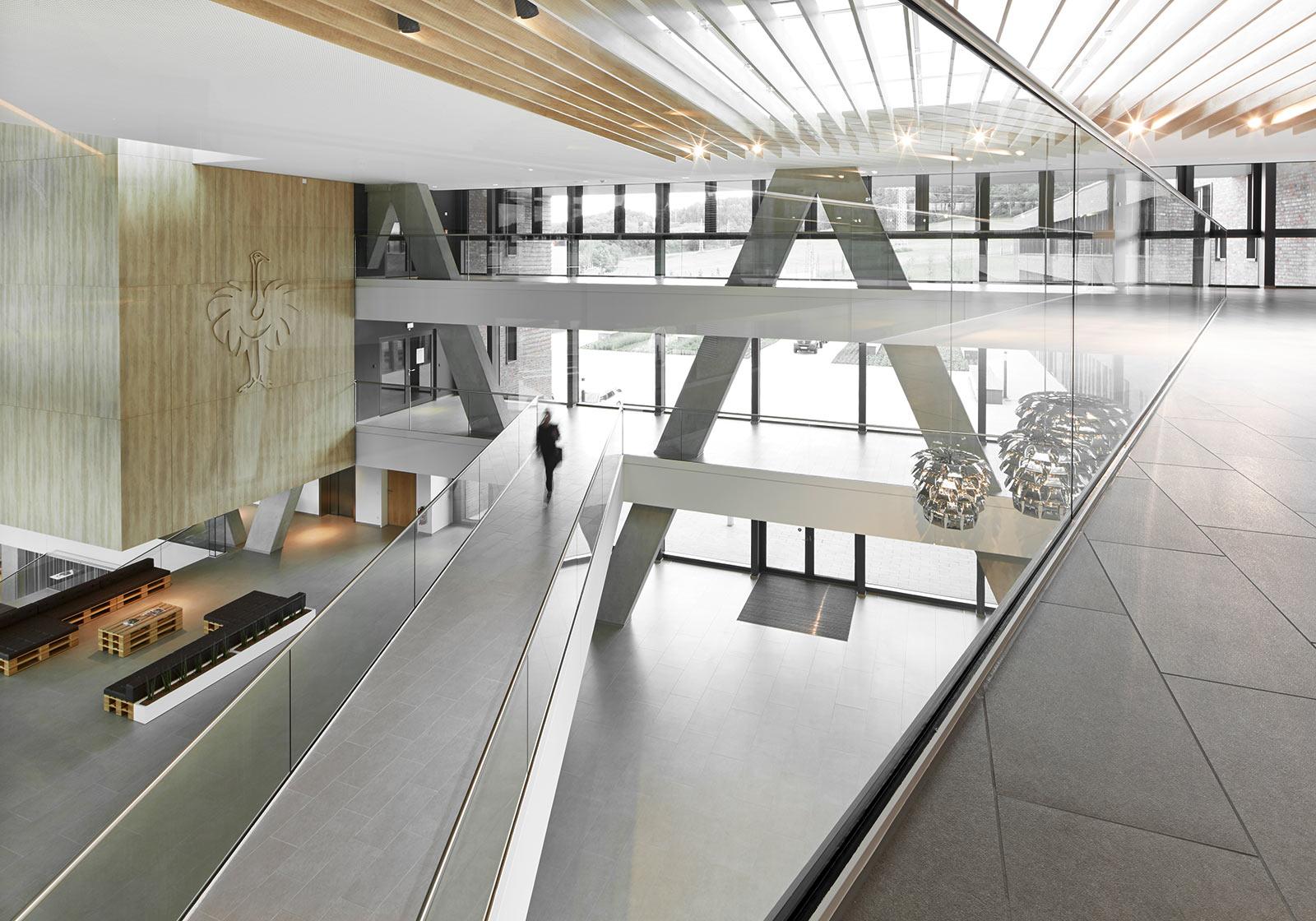 Das sichtbare Haupttragewerk ragt über 4 Ebenen. Glas, Holz und Sichtbeton unterstreichen den offenen, markanten Eindruck des Foyers. Foto: ATP/Becker