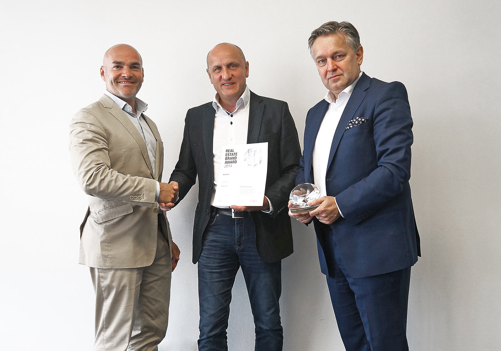 Photo: from left: Harald Steiner ceremoniously hands over the Real Estate Brand Award to Horst Reiner and Dario Travaš, ATP Vienna.