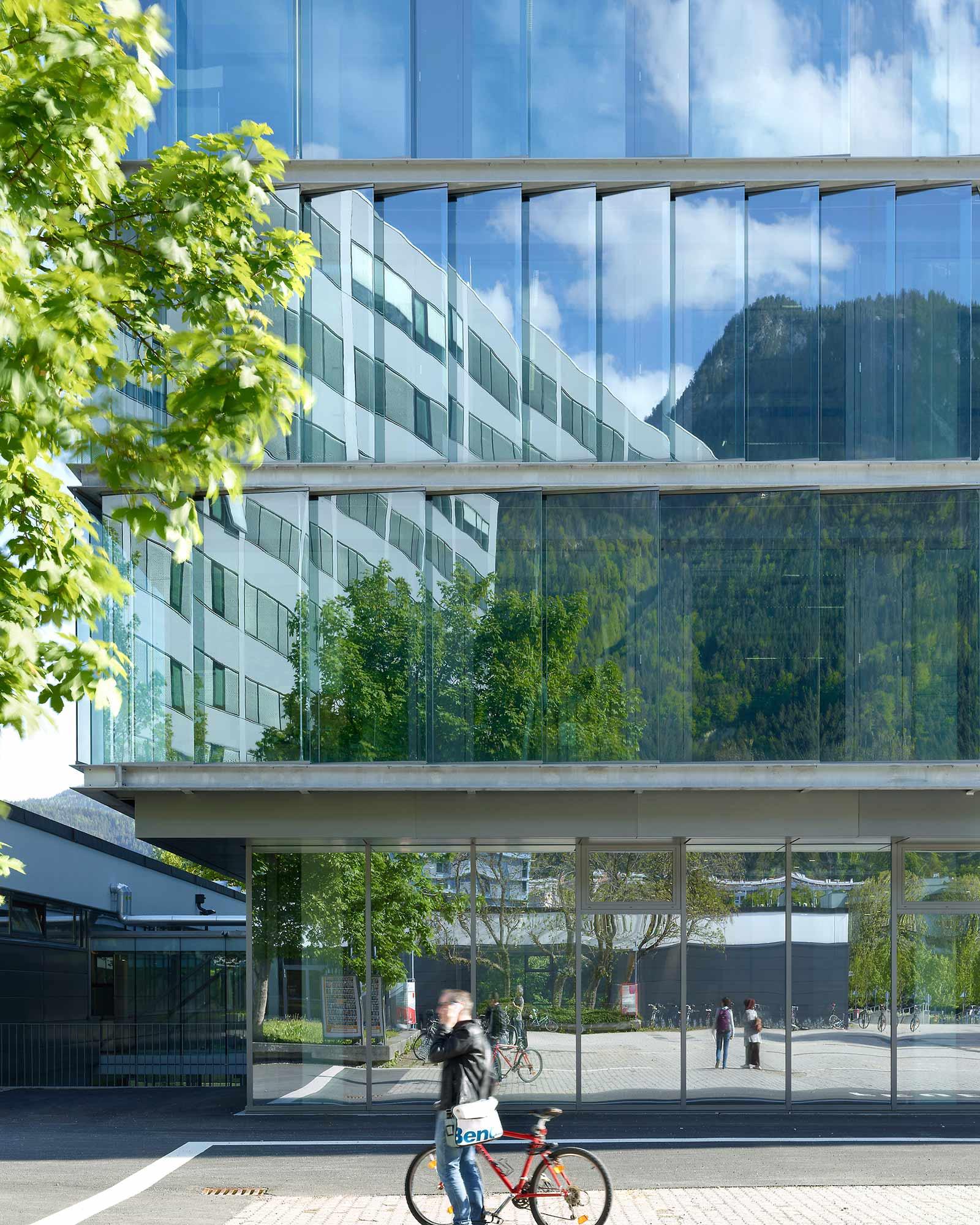 Wie gläserne Schuppen reihen sich an der Fassade der Architekturfakultät natürlich belüftete Glaselemente aneinander. Die Fakultät der Technischen Wissenschaften spiegelt sich darin. Foto: ATP/Jantscher